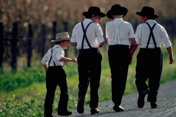 Four Amish boys walk and talk together.